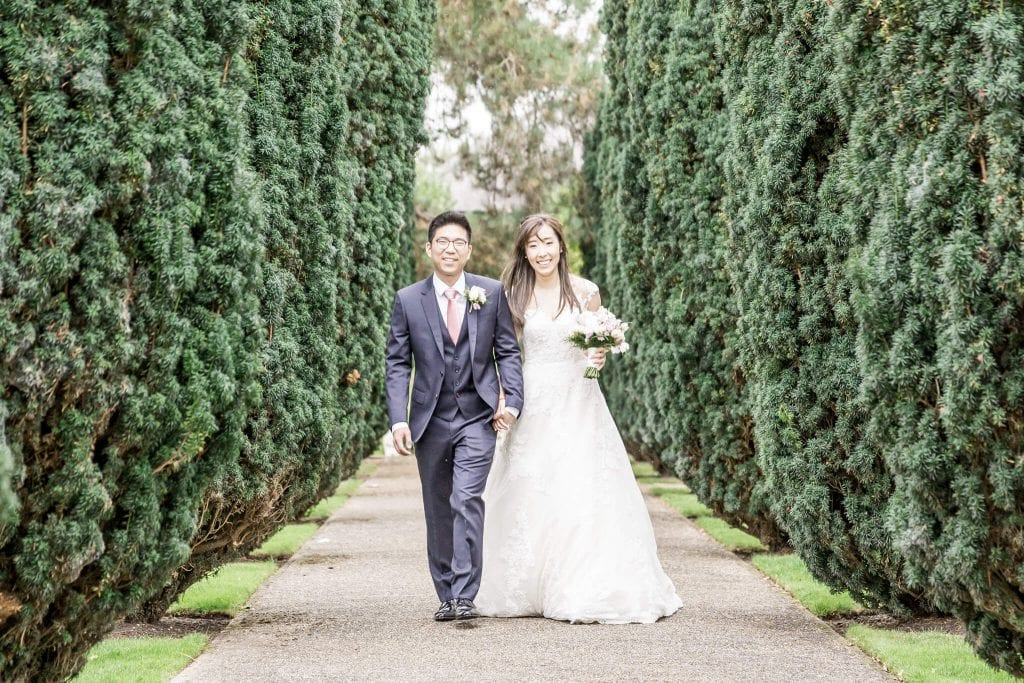 A bride and groom walk down an avenue of trees at Hertfordshire wedding venue The Grove.