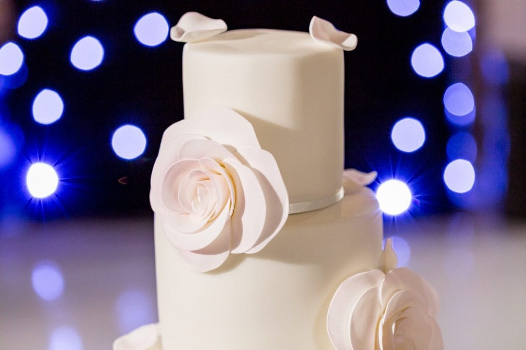 Wedding cake with roses photograph taken at The Grove at Hertfordshire by wedding photographer Natalie Chiverton