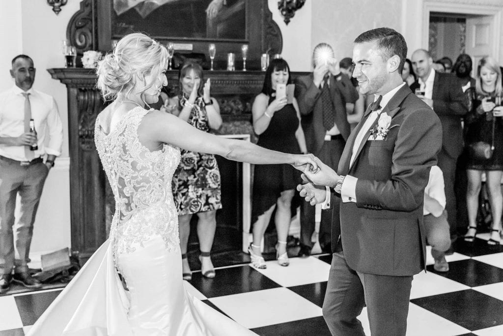A bride and groom have their first dance on a chequerboard dance floor at Hedsor House