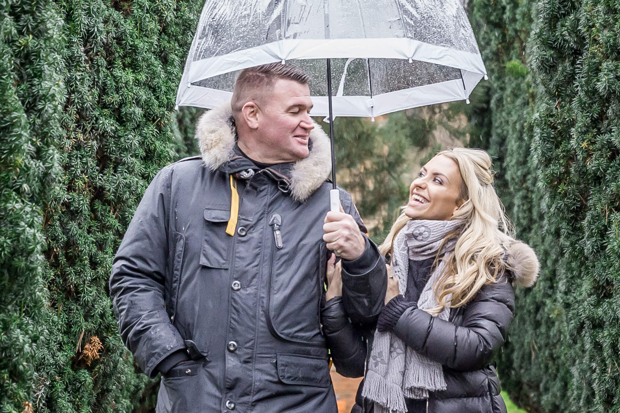 Couple under umbrella on a rainy day engagement photo taken at The Grove at Hertfordshire by Natalie Chiverton Photography