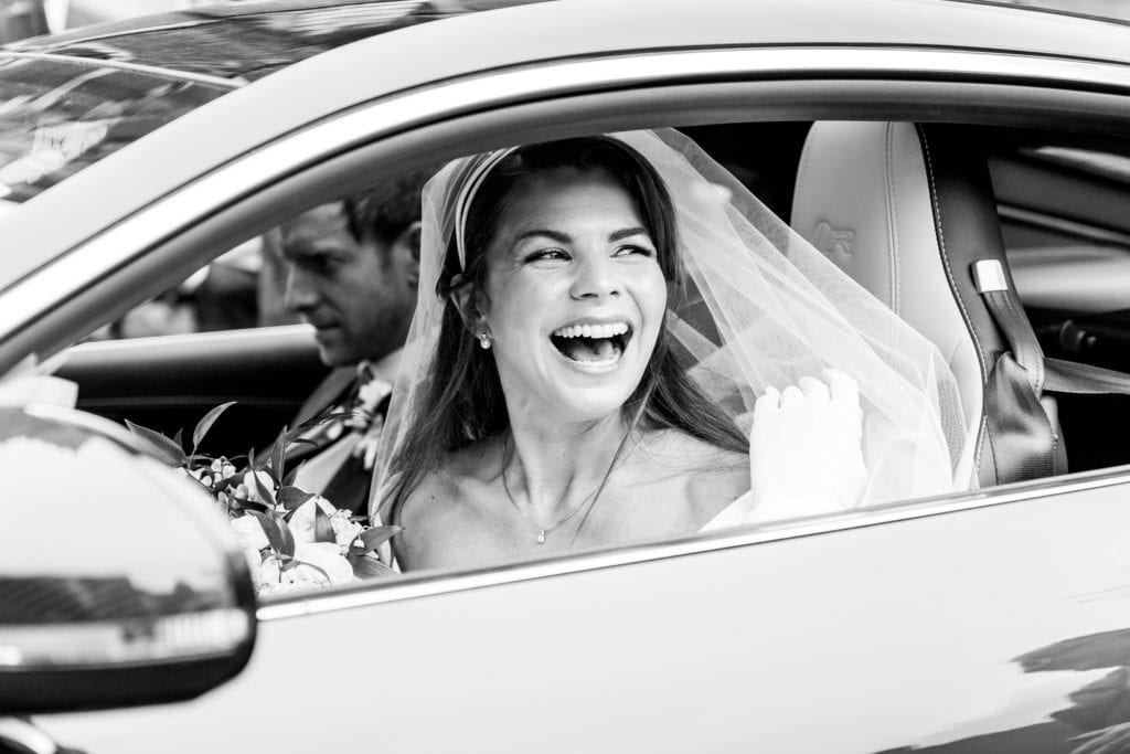 Bride in veil laughs out of the car window on her wedding day