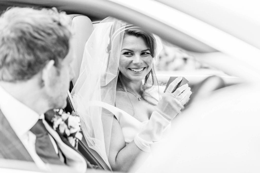 Bride and groom in front of car after their marriage ceremony