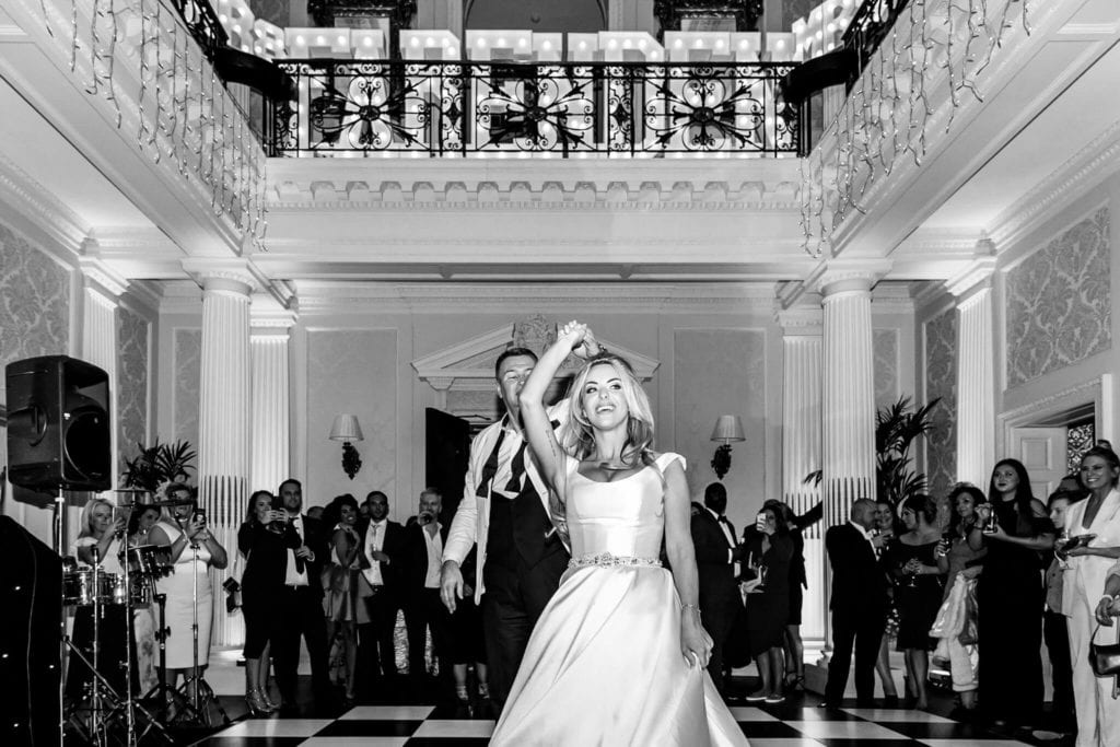 Black and white photo of bride taking her groom's hand up in the air at Hedsor House - Buckinghamshire taken by Hertfordshire wedding photographer Natalie Chiverton Photography