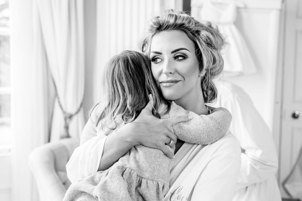 Bride holding a little girl tightly on her chest while getting her hair ready for the wedding at Hedsor House - Buckinghamshire taken by Hertfordshire wedding photographer Natalie Chiverton Photography