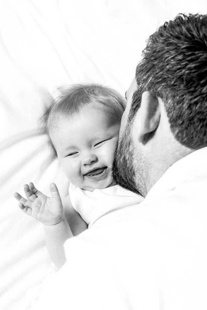 Black and white photo of a baby being kissed by her father and smiling at Kings Langley taken by Hertfordshire family photographer Natalie Chiverton Photography
