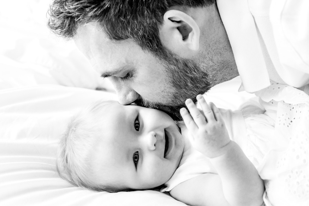 Black and white photo of a bearded father kissing his baby daughter's cheek while she is laying on her back on a bed at Kings Langley taken by Hertfordshire family photographer Natalie Chiverton Photography