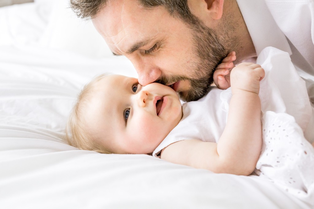 Photo of a bearded father kissing his baby daughter's cheek while she is laying on her back on a bed at Kings Langley taken by Hertfordshire family photographer Natalie Chiverton Photography