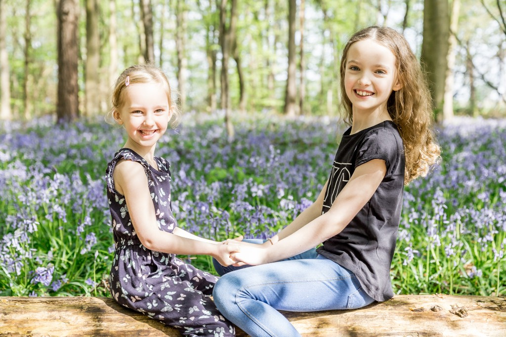 Two young girls holding each others hands while sitting on a old tree trunk with a beautiful bluebell field in the background at Whippendell Woods taken by Hertfordshire family photographer Natalie Chiverton Photography
