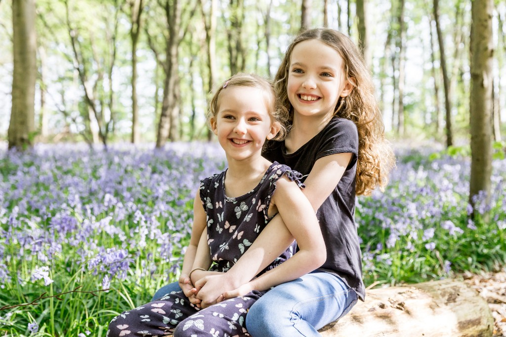 Two blonde sisters holding each other and sitting on a tree trunk with a field of bluebells in the background at Whippendell Woods taken by Hertfordshire family photographer Natalie Chiverton Photography