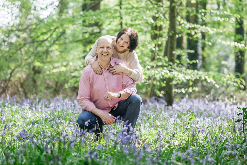 Couple with the husband sitting in the foreground and the wife holding him from behind in a bluebell field with trees in the background at Whippendell Woods taken by Hertfordshire family photographer Natalie Chiverton Photography