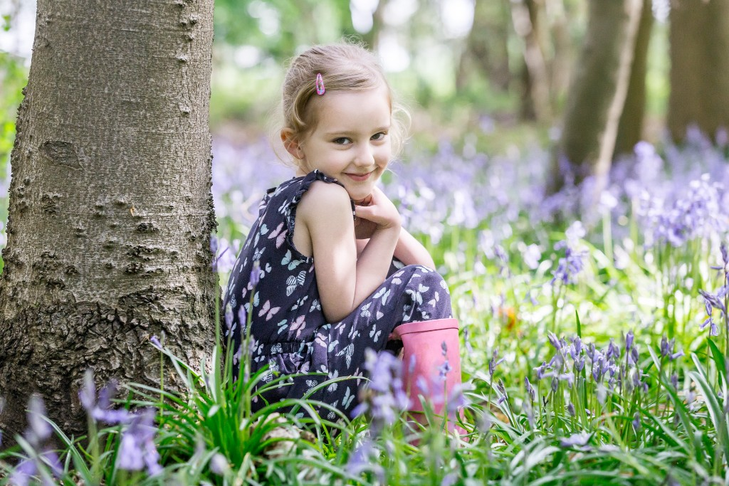 Beautiful young blonde girl sitting next to a tree in a field of bluebell shoots at Whippendell Woods taken by Hertfordshire family photographer Natalie Chiverton Photography