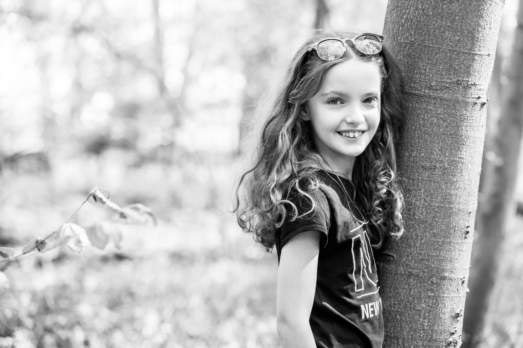 Black and white photo of a young girl resting on a tree and smiling happily towards the camera Beautiful young blonde girl sitting next to a tree in a field of bluebell shoots at Whippendell Woods taken by Hertfordshire family photographer Natalie Chiverton Photography