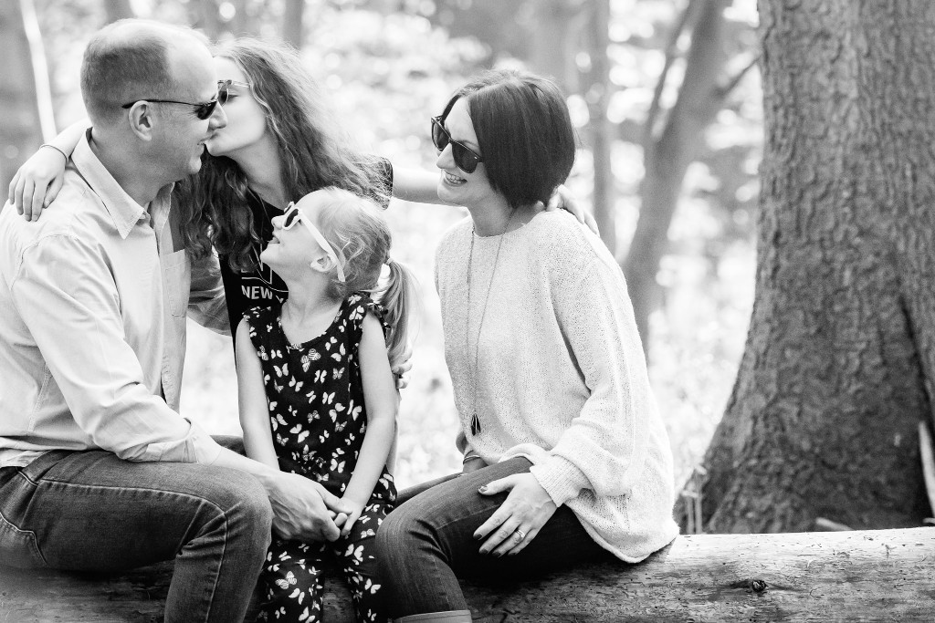 Black and white snapshot of a beautiful family moment with the father being showered with affection by his two daughters and his wife and sitting on a tree trunk in the forest Beautiful young blonde girl sitting next to a tree in a field of bluebell shoots at Whippendell Woods taken by Hertfordshire family photographer Natalie Chiverton Photography
