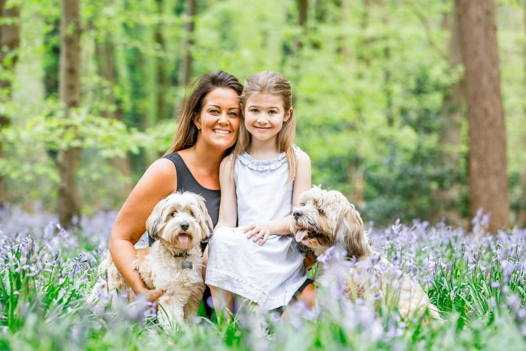 Mother and daughter with their two Bolonka dogs on either side in a field of bluebell shoots at Whippendell Woods taken by Hertfordshire family photographer Natalie Chiverton Photography