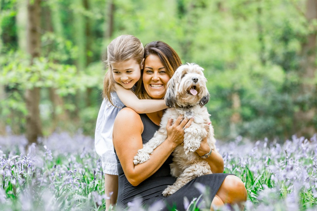 Daughter holding her mother from behind while the mother is holding a dog in her lap all resting in a bluebell field at Whippendell Woods taken by Hertfordshire family photographer Natalie Chiverton Photography