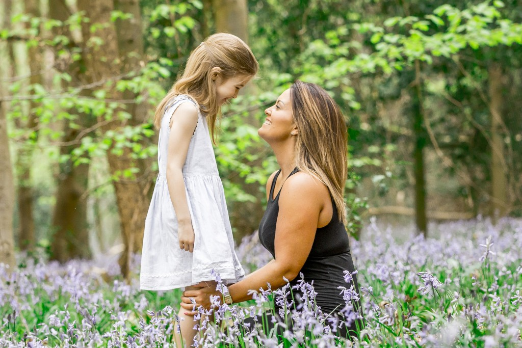 A mother kneeling in front of her daughter gazing lovingly at her in a bluebell field with trees in the background at Whippendell Woods taken by Hertfordshire family photographer Natalie Chiverton Photography