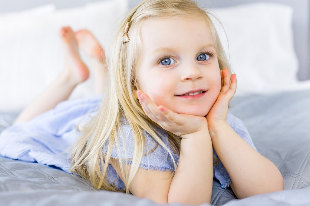 Beautiful blonde young girl with blue eyes holding her chin between her palms while laying on her tummy on a bed at Kings Langley taken by Hertfordshire family photographer Natalie Chiverton Photography