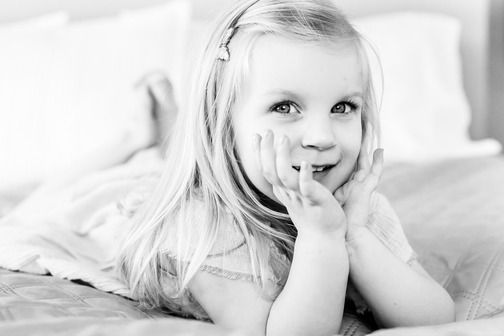 Black and white photo of a beautiful blonde young girl holding her chin between her palms while laying on her tummy on a bed at Kings Langley taken by Hertfordshire family photographer Natalie Chiverton Photography