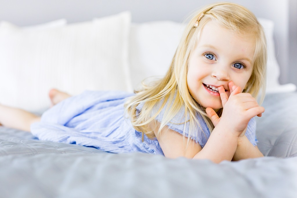 Beautiful blue eyed girl with long blonde hair wearing a blue dress and laying on her tummy on a bed at Kings Langley taken by Hertfordshire family photographer Natalie Chiverton Photography