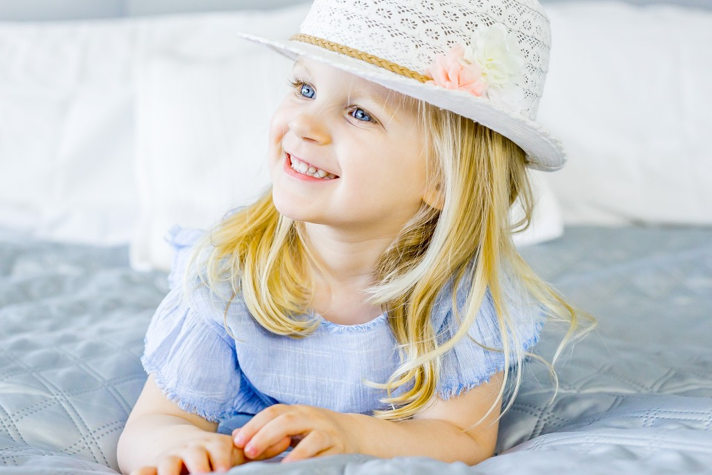 Beautiful blue eyed blonde little girl wearing a macramé hat and a blue dress while laying on her tummy on a bed at Kings Langley taken by Hertfordshire family photographer Natalie Chiverton Photography