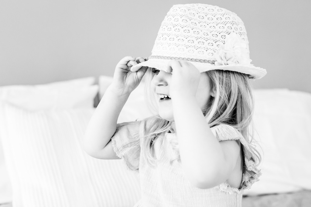 Black and white snapshot of a little girl holding her macrame hat's brim with both of her hands at Kings Langley taken by Hertfordshire family photographer Natalie Chiverton Photography
