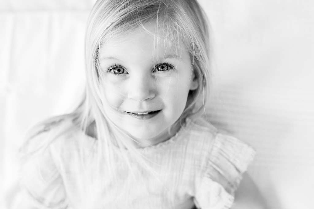 Black and white portrait of a beautiful young blonde girl with long hair and large gazing at the camera at Kings Langley taken by Hertfordshire family photographer Natalie Chiverton Photography