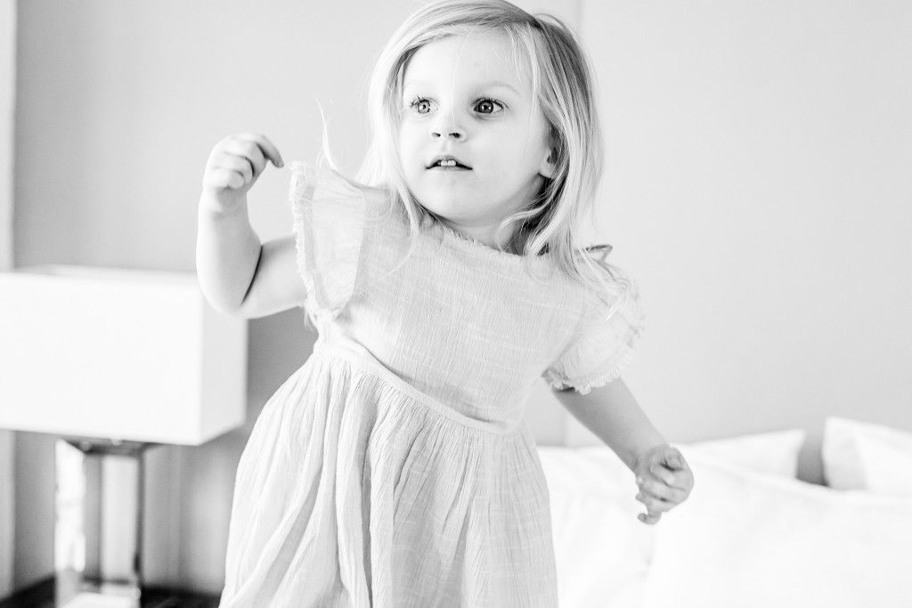 Black and white photo of a little girl wearing a dress jumping on a bed at Kings Langley taken by Hertfordshire family photographer Natalie Chiverton Photography