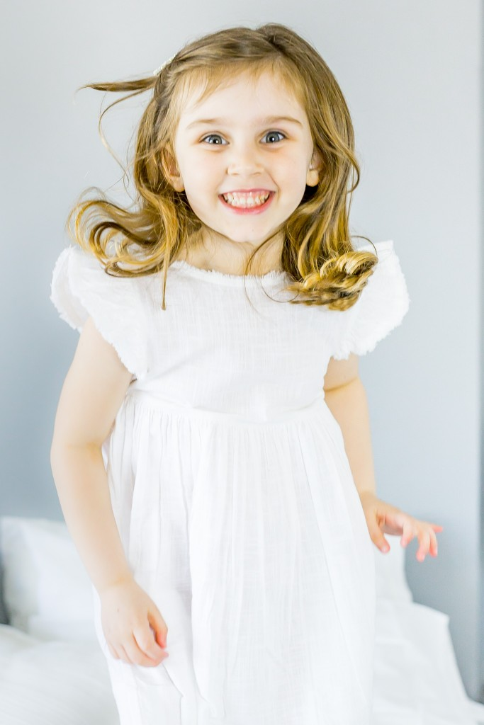 Golden haired young girl wearing a white linen dress smiling and jumping on the bed at Kings Langley taken by Hertfordshire family photographer Natalie Chiverton Photography