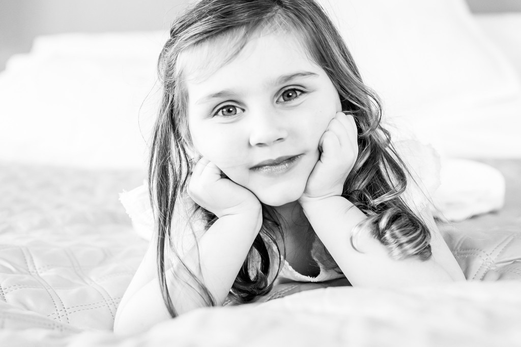 Black and white portrait of a young girl laying on her tummy and holding her head between her fists at Kings Langley taken by Hertfordshire family photographer Natalie Chiverton Photography
