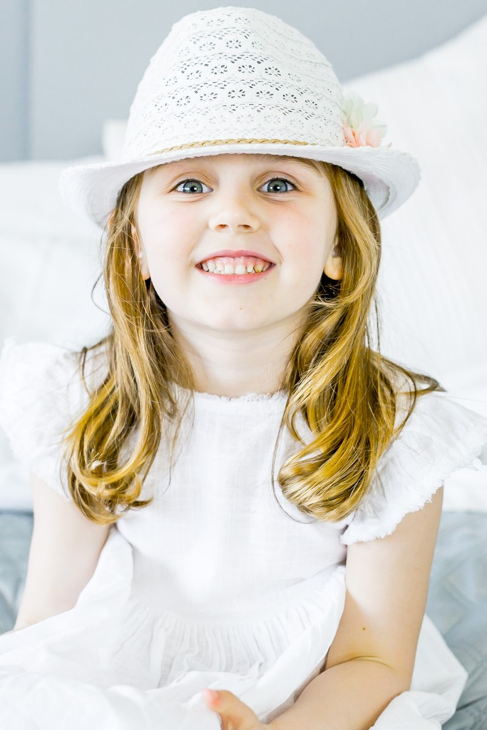Honey haired blue eyed girl wearing a white macramé hat and a white linen dress smiling for the camera at Kings Langley taken by Hertfordshire family photographer Natalie Chiverton Photography