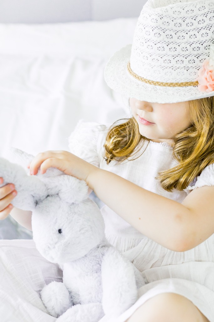 Snapshot of a young girl wearing a macrame hat and a white linen dress playing with her bunny toy while sitting on a bed at Kings Langley taken by Hertfordshire family photographer Natalie Chiverton Photography