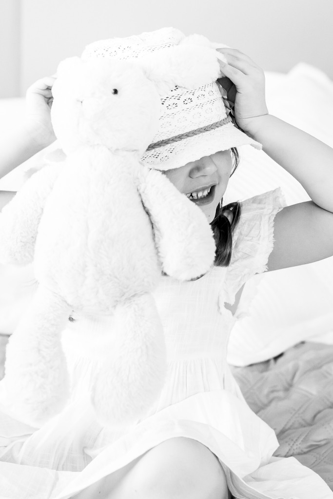 Black and white snapshot of a girl holding a white bunny toy with its ears wrapped around her macrame hat at Kings Langley taken by Hertfordshire family photographer Natalie Chiverton Photography