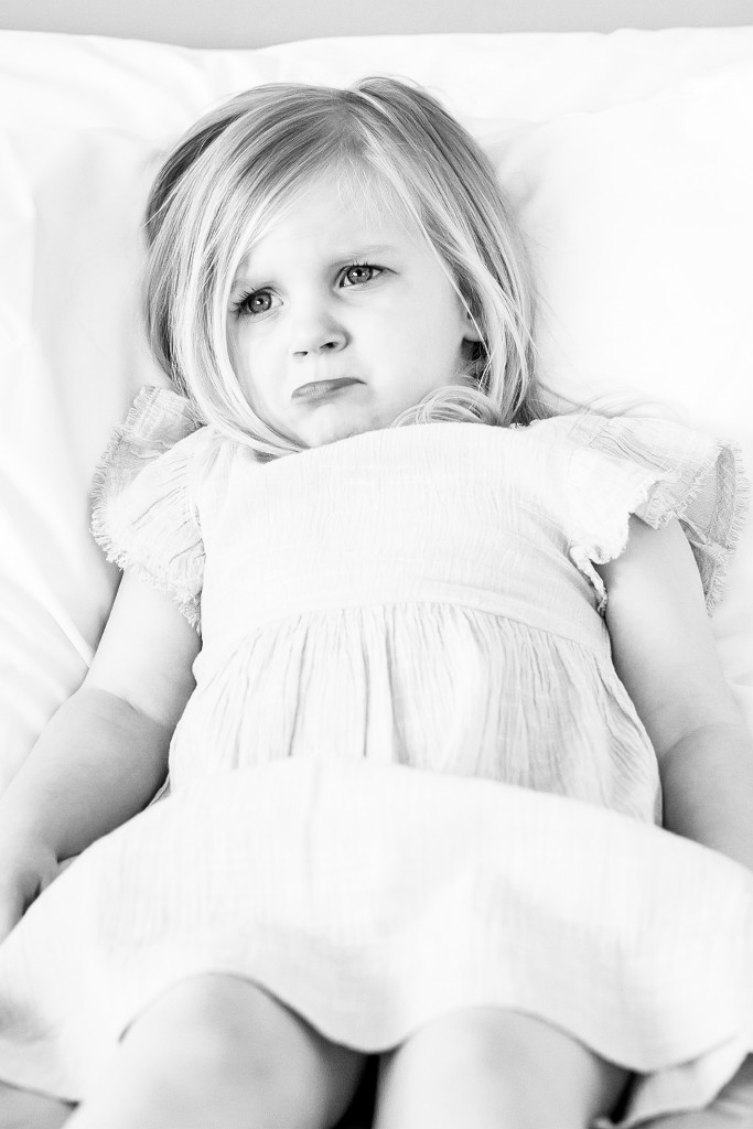 Black and white photo of a blonde girl wearing a white linen dress laying on the bed with her head on the pillow and pouting at Kings Langley taken by Hertfordshire family photographer Natalie Chiverton Photography