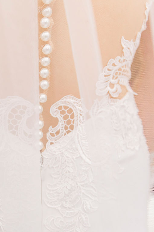 Bridal gown lace details and buttons with veil over the top.