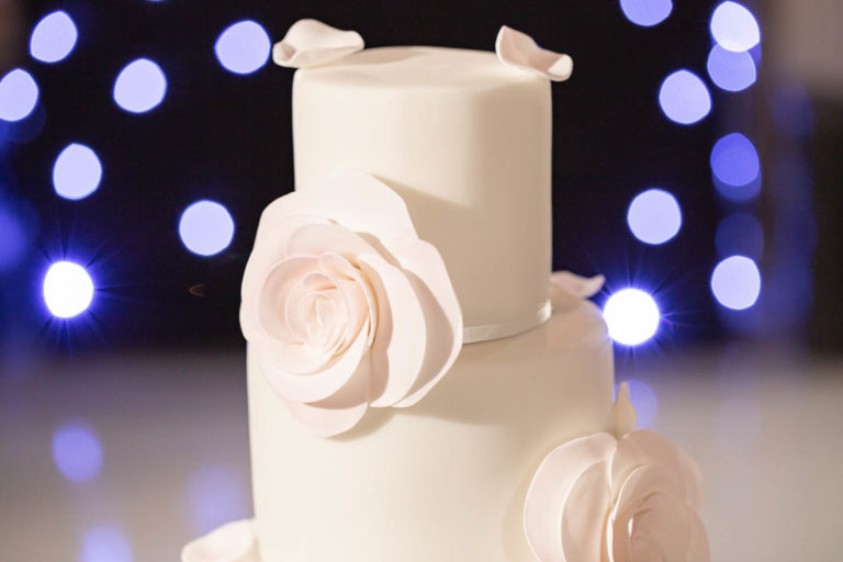 A three-tier white wedding cake with blush petal and flower icing details. The cake was chosen for a Chloe and Hobart's wedding at The Grove in Hertfordshire. Photo: Natalie Chiverton.