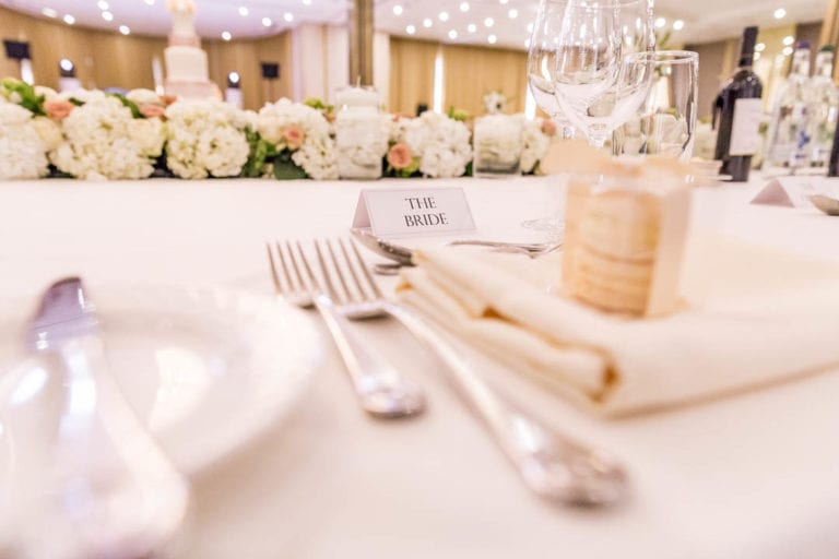 The bride's place setting on the long top table in the Amber Room at The Grove Hertfordshire.