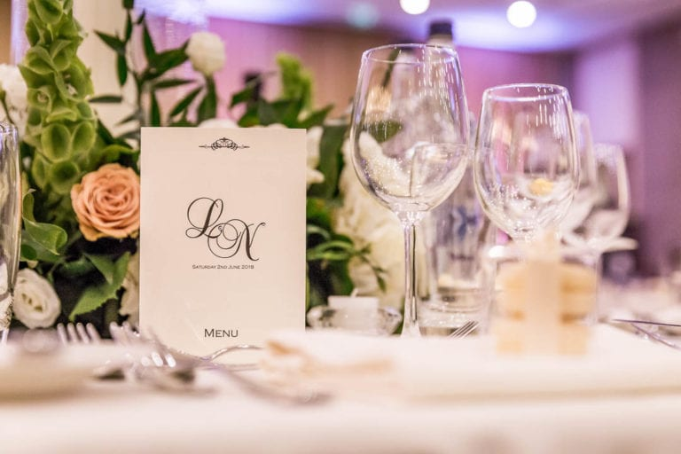 Initials adorn the menu at a wedding breakfast in the Amber Room at The Grove Hertfordshire. The five star wedding venue has multiple spaces which can be used for wedding ceremonies and receptions.