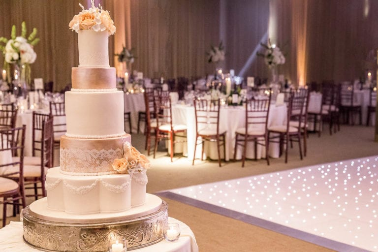 A wedding cake sits beside the dance floor in the Amber Room at Hertfordshire's The Grove, waiting for the bride and groom to cut it.
