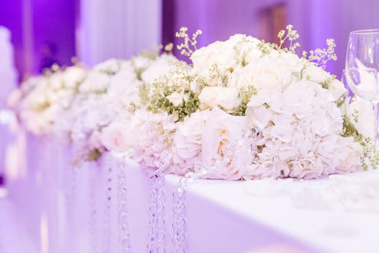 White florals decorate the top table at a wedding breakfast in the Amber Suite at Watford's The Grove Five Star Hotel.