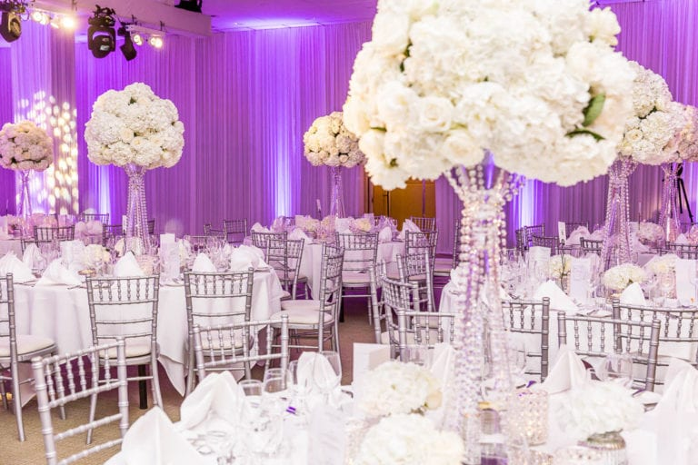 Tall white floral arrangements suspended in clear glass vases decorate a wedding breakfast in the Amber Room at The Grove - a Hertfordshire wedding venue. Wedding photographer at The Grove - Natalie Chiverton.