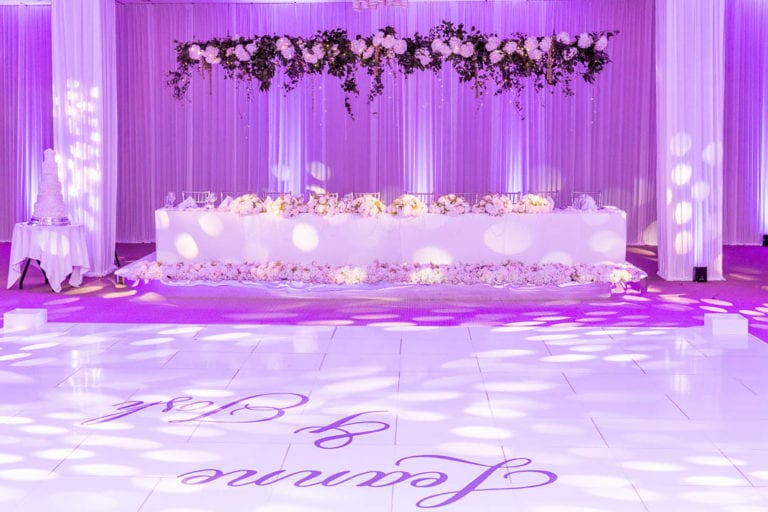 Suspended florals over the top table at a wedding reception at The Grove in Hertfordshire. The couple names are on the dance floor.