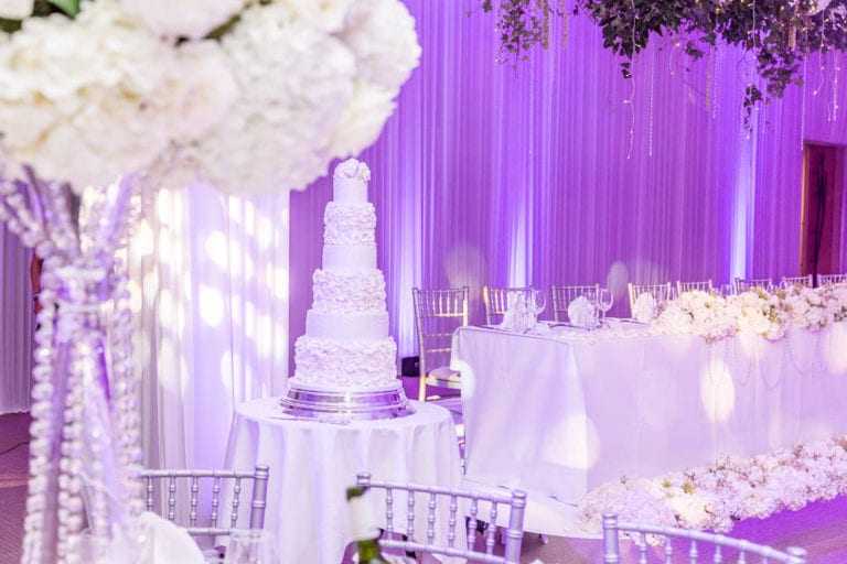 A white, five-tier wedding cake waits for the bride and groom to cut it. Wedding photographer: Natalie Chiverton.
