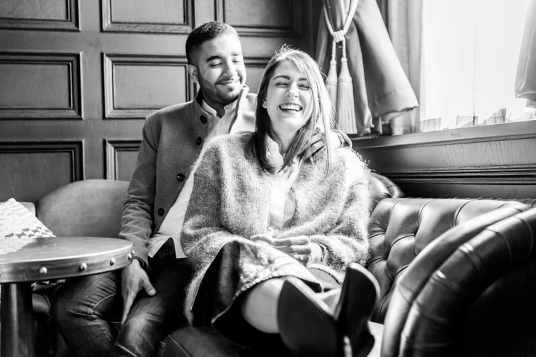 A couple sit on a Chesterfield sofa in the Kimpton Fitzroy Hotel in Bloomsbury, London, during their engagement portrait shoot. They're giggling and having fun.