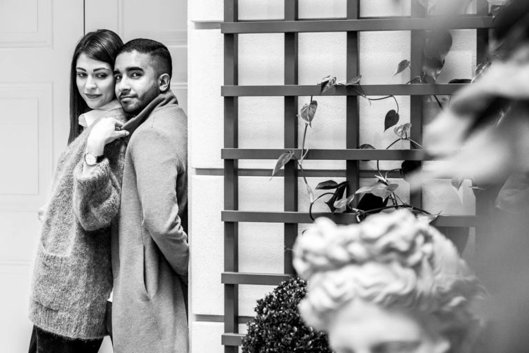 Engagement shoot pose: stand in front of your fiance while he leans against a wall. This is in the Kimpton Fitzroy hotel in London's Russell Square, Bloomsbury.