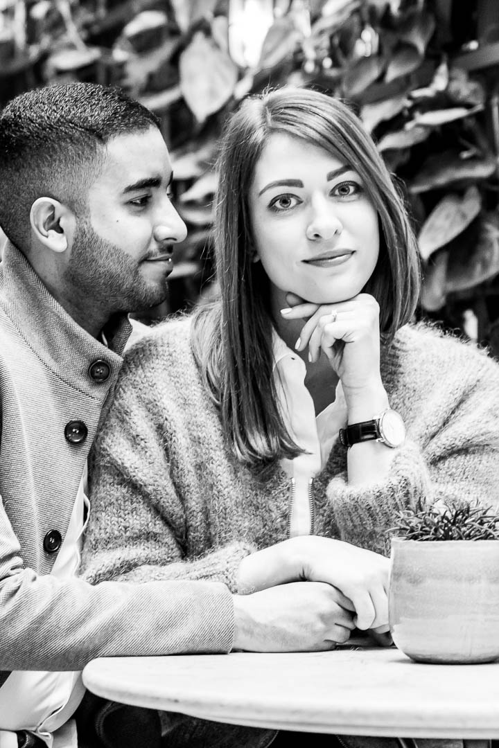 Engagement portrait pose: a couple sit at a table in a garden room, looking directly at the camera.