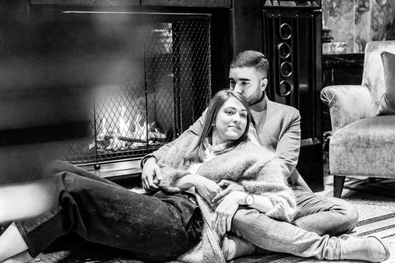 A couple lounges in front of a fire in the Kimpton Fitzroy Hotel in London's Russell Square as part of their engagement portraits by London engagement photographer Natalie Chiverton.