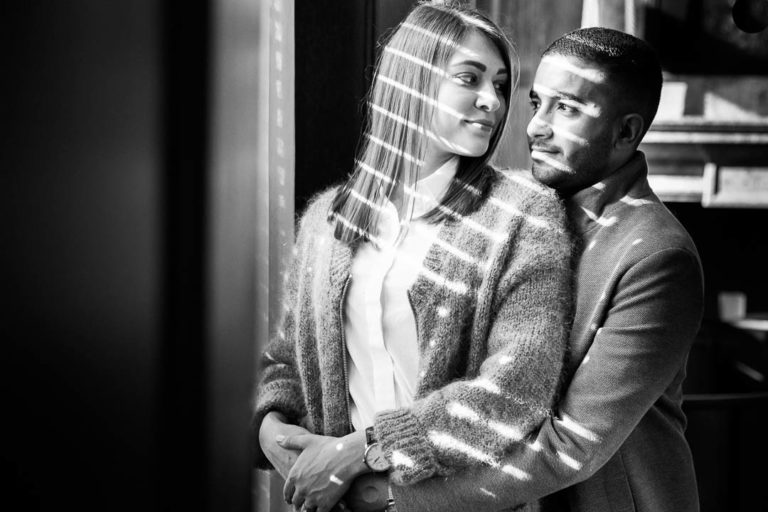 Shafts of light fall across this couple, adding drama to their engagement portraits. They were in the Kimpton Fitzroy Hotel in London's Russell Square, in Bloomsbury.