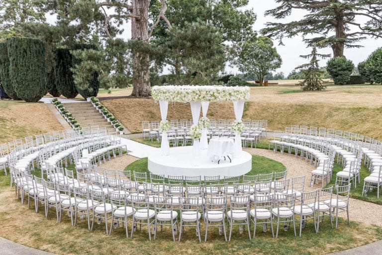 The Sunken Garden at The Grove in Hertfordshire - ready for a wedding ceremony with the bride and groom on a central platform, surrounded by their family and friends. Photographer: Natalie Chiverton.