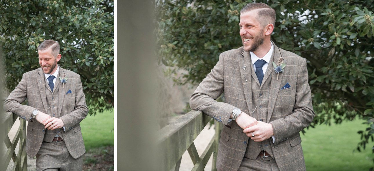 A groom wearing a tweed suit leans on a rustic wooden gate near Great Tythe Barn on the morning of his wedding.