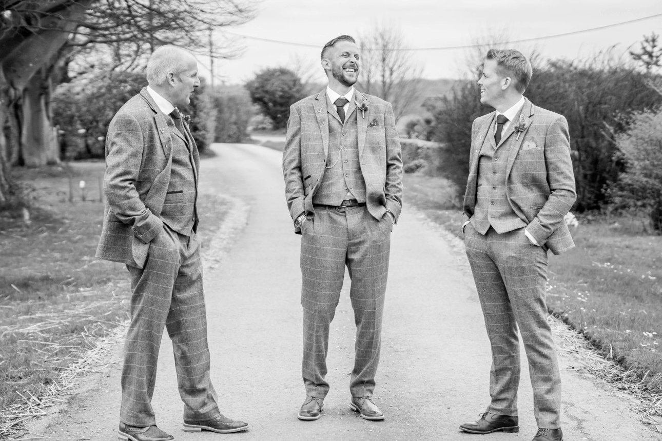 Black and white photo of the groom and groomsmen on the wedding morning, hands in pockets. They're wearing tweed suits and standing on a country lane near the Great Tythe Barn Tetbury in Gloucestershire.